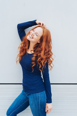 Slender sexy young woman with curly long red hair