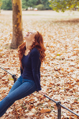 Young carefree redhead woman relaxing in a park