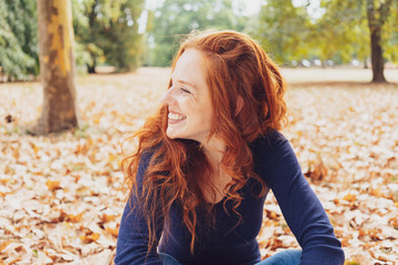 Cute happy woman relaxing in a park in autumn