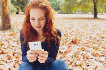Attractive young woman sitting reading an sms