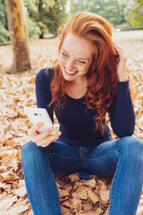 Happy young woman relaxing in an autumn park