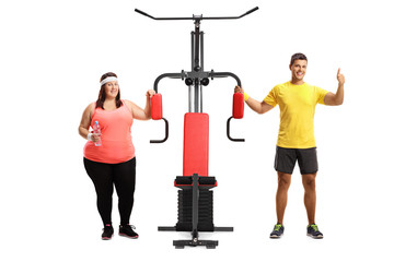 Overweight woman and a male fitness instructor standing next to an exercise machine