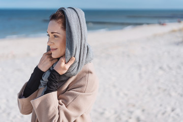 Young smiling woman with scarf standing on beach