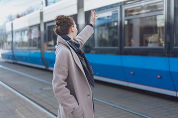 Stylish woman waving at a passing tram