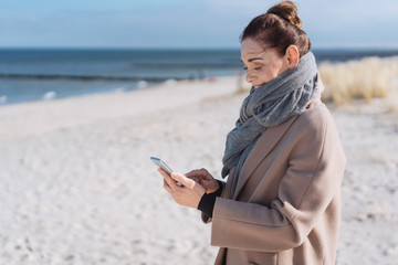 Woman enjoying the winter sunshine at the beach