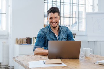 Young smiling man sitting in front of laptop