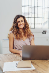 Smiling woman sitting in front of laptop