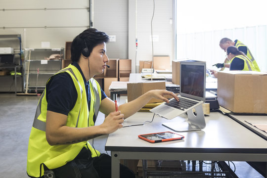 Confident young male customer service representative looking away while sitting with laptop at desk in warehouse