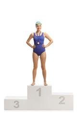 Female swimmer at a winner's pedestal wearing gold medal