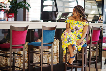Cute small height african american girl with dreadlocks, wear at coloured yellow dress, sitting on cafe at shopping center.