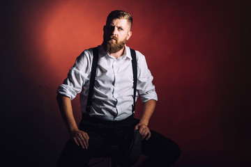 Portrait on a bearded man in white shirt and suspenders on black background in studio