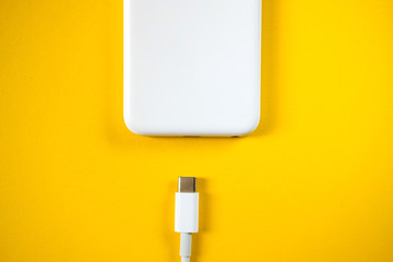 Smartphone Connects to Charger through  Cable on Yellow Background. Top View. copy Space for insert text.