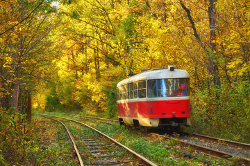 Red retro tram goes along the route