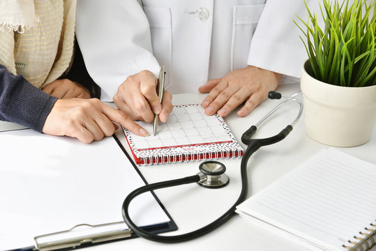 Hospital and health care concept, Doctor and patient make an appointment for follow up plan, Physician point at a calendar.