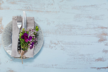 Rustic table setting with purple flowers on light wooden table.