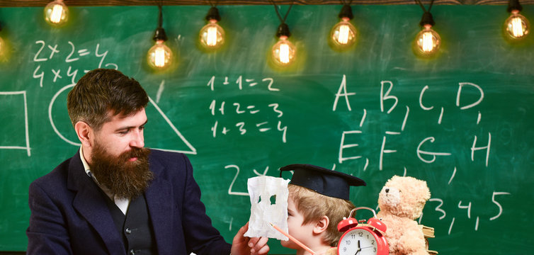 Educational games concept. Boy, child on cheerful face holds crumpled paper as mask while teacher talk to kid. Teacher with beard, father teaches little son in classroom, chalkboard on background.