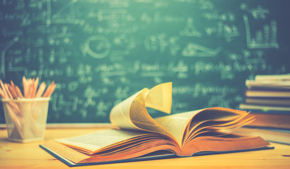 School books on desk formulas and Physics inscription on the blackboard , education concept