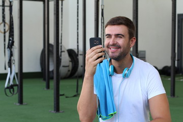 Distracted man with cellphone at the gym