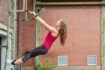 Sportliche junge Frau klettert auf einer Leiter