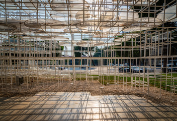 Abstract modern art steel framework giving shade in public park in Albania.