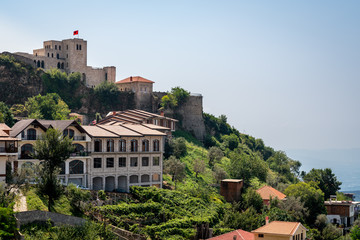 Beautiful mountain landscape view of ancient castle and buildings on green mountain side in Albania eastern Europe.
