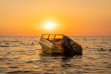 Close beautiful sea view of orange and yellow sunset with a moored motorboat against the horizon.
