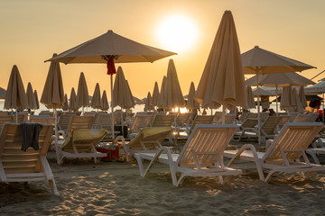 Beautiful yellow sky and many sunchairs, sun umbrellas and parasols on a beach in Albania late afternoon.