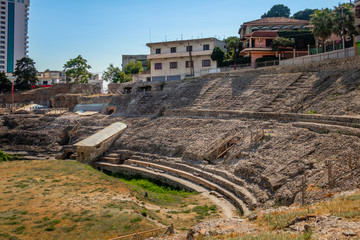 Exterior of ancient Roman amphitheater with surrounding buildings in the city of Durres Albania.