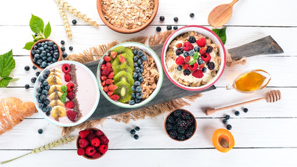 Large Assortment of porridge with fruit and berries. Breakfast. On a white wooden background. Top view. Free space for text.