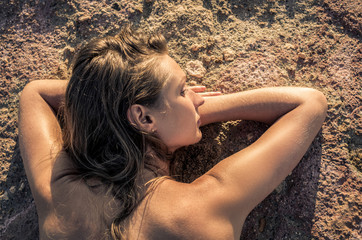 Portrait of a young woman sunbathing lying on rocks