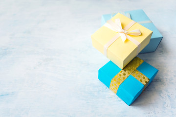 three Yellow and blue gift box with white ribbon and bow on light blue watercolor pastel table background. Minimal festive winter gift background