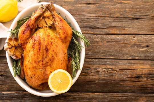 Whole roasted chicken with lemon and rosemary on a black plate. Rustic style. Christmas concept. Christmas turkey.