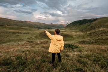 A young guy in a yellow raincoat on top of a mountain. Carpathians, Ukraine