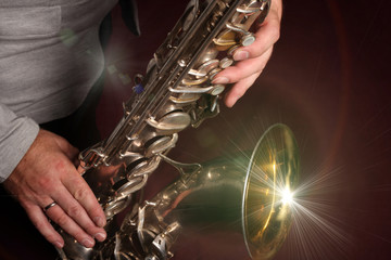 Photo sur Aluminium Musique Man's hands with saxophone on burgundy background