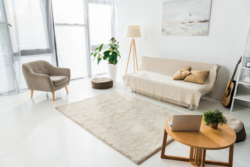 interior of modern living room with laptop, carpet and furniture
