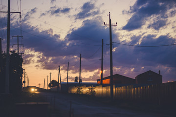 Sunset sky over the empty outskirts. View of the country street at dusk. Tinted photo