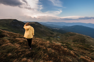 A young woman in a yellow raincoat on top of a mountain. Carpathians, Ukraine