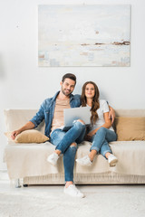 smiling young couple sitting on sofa with laptop at home