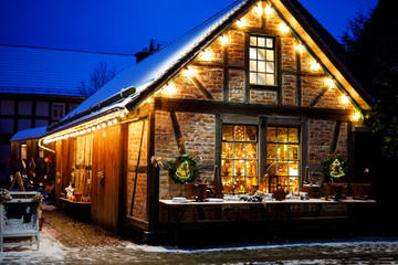 Decorated house on Christmas in Germany covered with snow. Festive lights, garlands. Beautiful holiday season