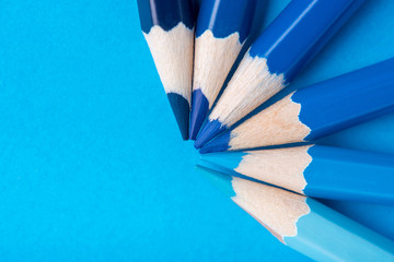 Macro photograph of several pencils of blue color on a paper background