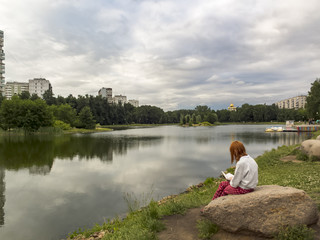 Girl reading a book sitting on a stone in the Park