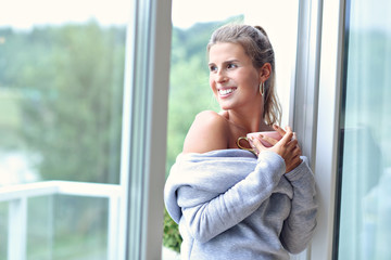 Adult woman wearing warm sweater resting at home one autumn day