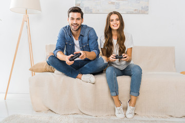 smiling young couple playing video game by joysticks on sofa at home