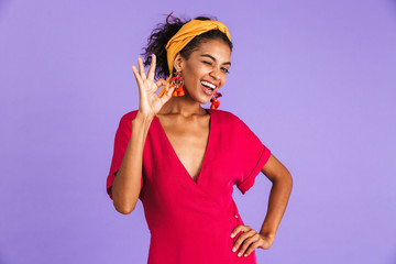 Image of cheerful happy woman 20s in hair band smiling and showing ok sign, isolated over violet background