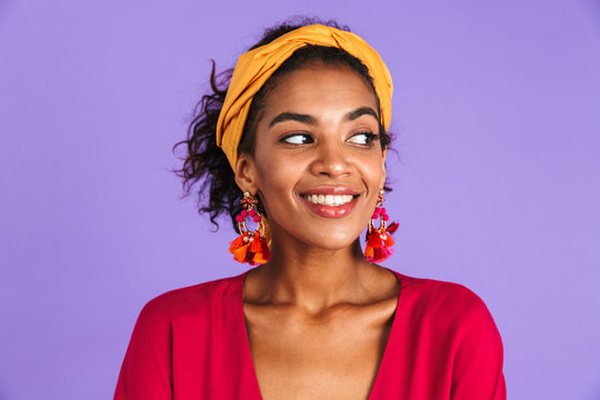 Image of charming woman 20s in hair band and earrings smiling and looking aside, isolated over violet background