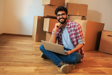 Young man moving into a new house.He sitting on floor in empty apartment and calculate home budget.