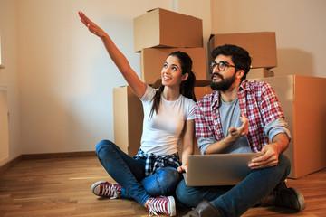 Young couple moving into a new house.They unpacking and finding ideas for interior design.