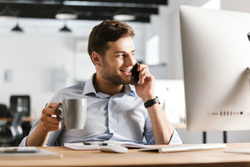 Smiling business man talking by smartphone and drinking coffee