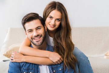 portrait of young happy couple looking at camera at home
