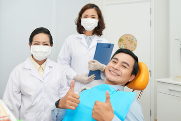 Asian cheerful man showing thumbs up in dental chair with Asian women in medical gowns standing near
